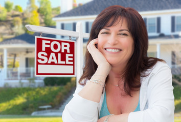 Middle Aged Woman In Front of House with For Sale Real Estate Sign In Yard