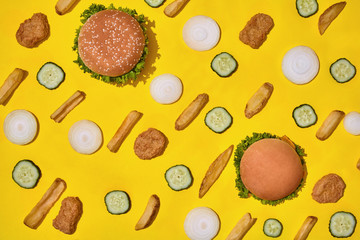 Most popular fast food meal. Chicken nuggets, burgers and french fries on yellow background top view