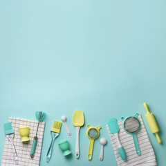 Pastel yellow, blue cooking utensils on turquoise background. Food ingredients. Cooking cakes and baking bread concept. Copy space. Top view. Flat lay