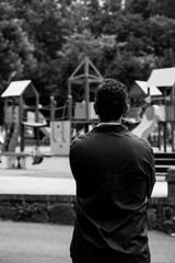 Worried man looking to a empty city playground. Converted to black and white, grain added.