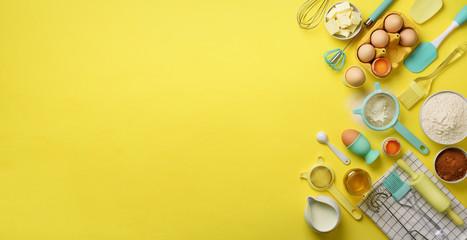 Banner of baking ingredients - butter, sugar, flour, eggs, oil, spoon, rolling pin, brush, whisk, towel over yellow background. Bakery food frame, cooking concept. Top view, copy space. Flat lay