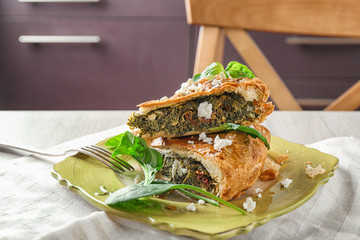 Tasty pie with spinach on plate