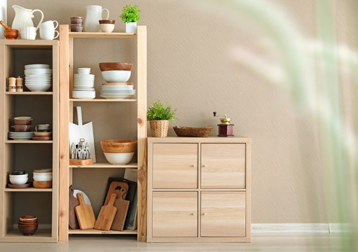 Storage stand with ceramic and wooden kitchenware on light wall background