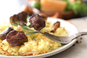 Plate with tasty risotto and mushrooms on table, closeup