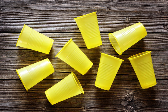 Disposable yellow plastic cups on a wood background