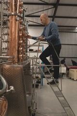Male worker checking machine of distillery