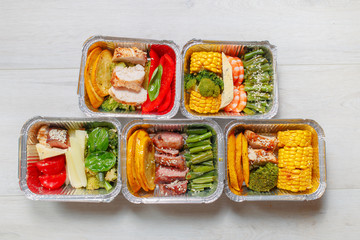 Healthy meal prep containers with vegetables, chicken, beef and shrimp grilled. Close-up, view top.