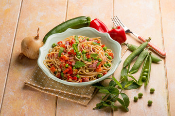 spaghetti with bacon capsicum peas and zucchinis