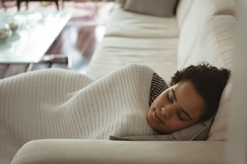 Woman wrapped in blanket sleeping on sofa