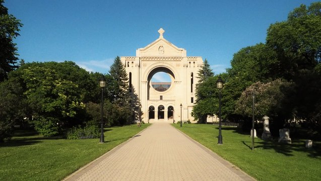 Saint Boniface Cathedral contrasted against a bright blue sky on a sunny day in Winnipeg, Manitoba, Canada.  This building serves as the principal church for Eastern Manitoba.