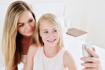 Portrait of beautiful mature mother and her daughter making a selfie using smart phone and smiling