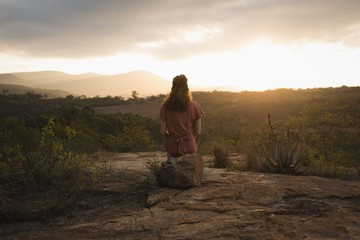 Woman sitting on rock and looking at nature