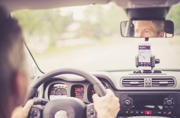Auto Cockpit von innen, Interieur, Hände am Lenkrad, Smartphone in Handyhalterung, Navigation