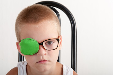 Child in glases with green Occluder. Ortopad Boys Eye Patces nozzle for glasses for treating strabismus (lazy eye).Nine years old boy with one eye covered by eye pad and with eye glasses.