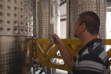 Male worker examining gin in measuring cylinder
