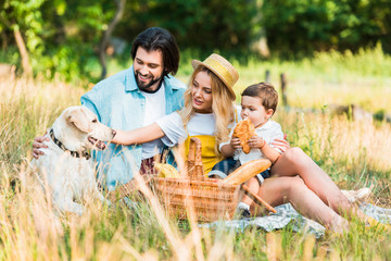 parents and son sitting on blanket at picnic and palming dog