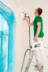 Man painting walls with paint spray gun.