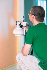 Man painting an interior wall using a spray gun.
