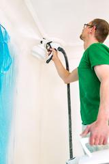 Man painting walls using spray gun.