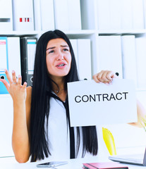 Young angry business woman ripping contract at the desk, break the rules - failure business concept.