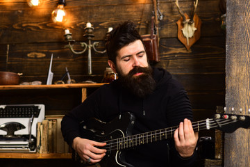 Man bearded musician enjoy evening rehearsing performance at home, wooden background. Boost your skills. Guy in cozy warm atmosphere learn new song chords. Man with beard holds black electric guitar