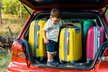 adorable toddler boy standing with travel bags in car trunk