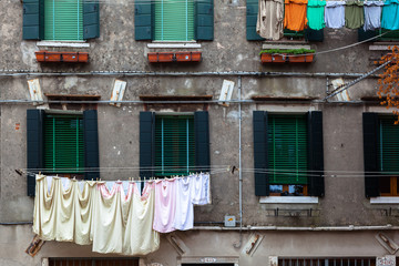 The smooth fabrics drying on clothes line contrast with the rough building texture. Venice, Italy