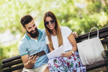 Young attractive couple talking and looking at digital tablet.