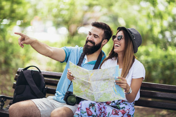 Happy tourist couple looking at map on a bench in the park on a sunny day