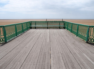 the end of the victorian pier at St Annes on sea in lancashire looking out onto the beach at low tide with the sea in the far distance on a bright summer day