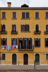 Yellow venice building with colorful laundry hund out to dry