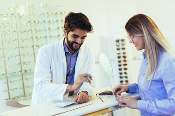 Woman choosing her new glasses at optics store with help of ophthalmologist