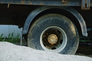 Stuck in the sand dirty wheel of a truck. Close-up.