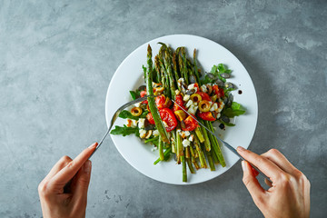 First person view on a dish with roasted asparagus, tomatoes, olives, cheese and arugula.