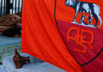 A migrant lies on a street as he is covered with an AS Roma soccer flag after migrants are being removed from a building where they had been living in Rome