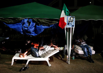 Migrants are seen on a street after being removed from a building where they had been living in Rome