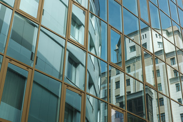 The modern building is reflected in the facade of another building