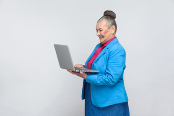Aged woman standing and holding laptop and looking at screen with satisfied face. Grandmother in light blue suit and collected gray hair bun hairstyle. indoor, Studio shot, isolated on gray background