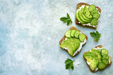 Healthy rye toasts with soft cheese, avocado and cucumber.Top view with copy space.
