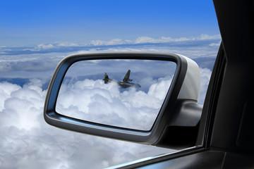 Samolot wojskowy nad chmurami w lusterku samochodu osobowego.