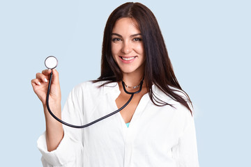 Photo of attractive brunette young female pulomonologist listens patient`s lungs, diagnoses acute bronchitis, wears lab coat, stands against light blue background. Medicine and treatment concept