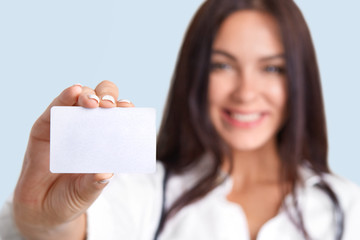 Horizontal shot of medical worker holds blank card, blurred silhouette, free space for your name and surname. Cute female nurse holds name tag. Professional young woman therapist stands indoor