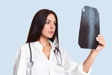 Serious female doctor looks attentively at X ray, examines people`s spine, wears white lab gown, has phonendosope on neck, stands sideways against light blue background. Medical treatment concept