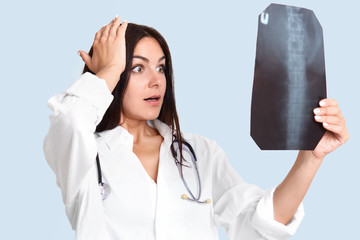 Stunned beautiful brunette young professional female doctor holds hand on head, holds X ray picture, studies backbone, shocked to notice serious disease, isolated on blue background. Medicine concept