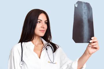 Indoor shotof pleasant looking female nurse or doctor looks attentively and happily at X ray, studies skeleton, dressed in white medical robe. Professional radiologist in hospital. Health care concept