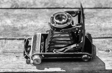 Old camera in the image of an old car abstraction on a wooden background. Black and white photo of an old camera abstraction in the form of an old car