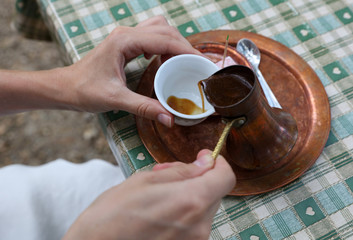 Woman drinking coffee served in a traditional l turkish pot close up