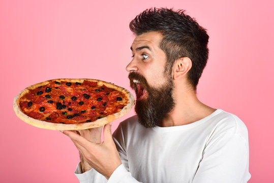 Man eating pizza. Bearded man hipster with pizza. Food, lunch and people concept - happy hungry man holding baking sheet with delicious pizza in hands. Satisfed guy in white shirt enjoy tasty pizza.