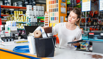 Young female seller standing at the counter in household tools store