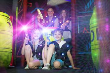 Kids sitting in beams with laser guns